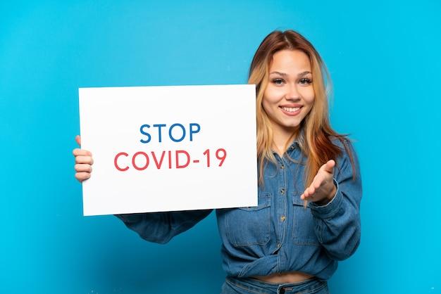Menina adolescente isolada segurando um cartaz com o texto pare covid 19 fazendo um acordo