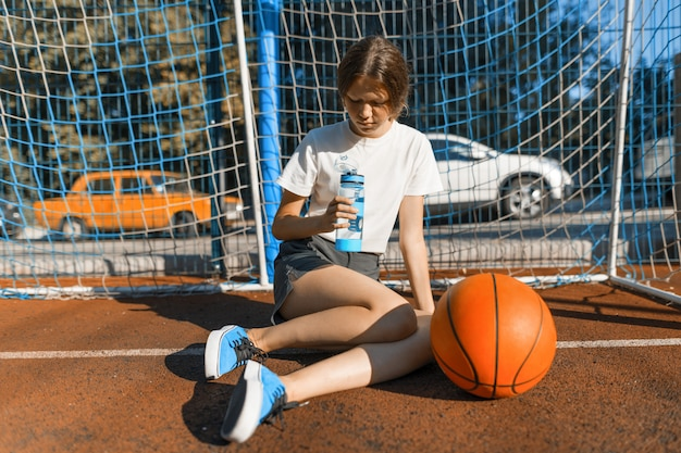 Menina adolescente jogando basquete de rua com bola