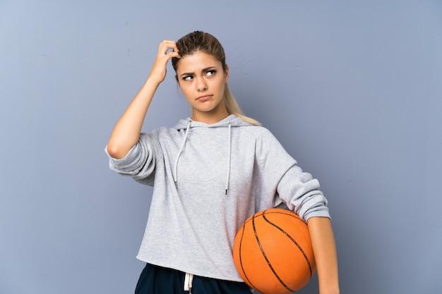 Menina adolescente jogando basquete na parede cinza, tendo dúvidas e com a expressão do rosto confuso