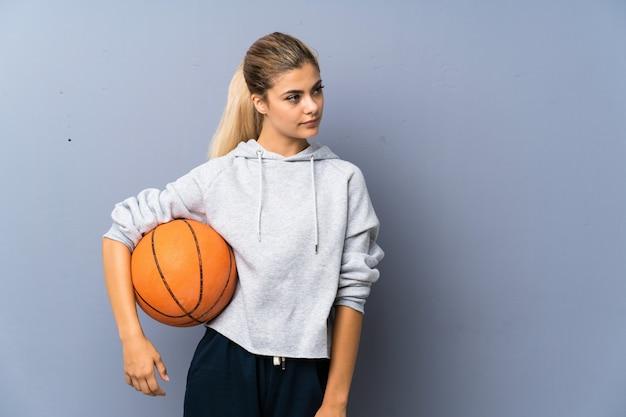Menina adolescente jogando basquete na parede cinza