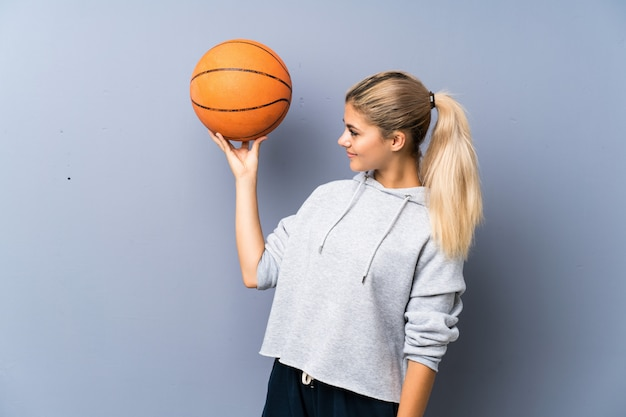 Menina adolescente jogando basquete sobre a parede cinza