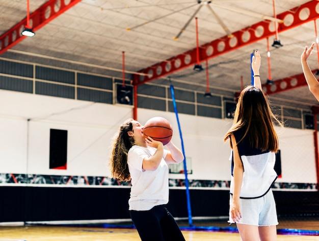 Menina adolescente, jogando basquetebol, fazer um passe