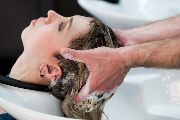 Menina adolescente, lavando cabelo, em, cabeleireiro, piscina