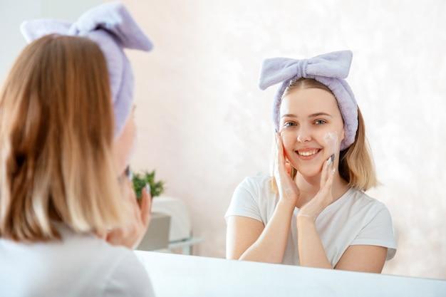 Menina adolescente lavando o reflexo do retrato do rosto no espelho no banheiro da manhã. jovem mulher loira aplica limpador facial para lavagem da pele. rotina de banho matinal de autocuidado.