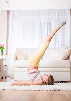 Menina adolescente, levantando as pernas no quarto
