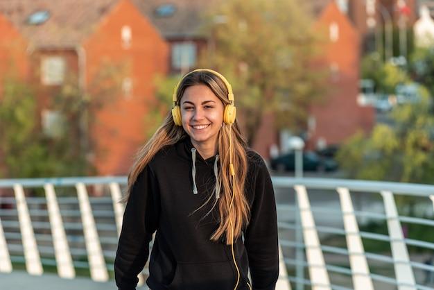 Menina adolescente loira com fones de ouvido amarelos, ouvindo música enquanto caminhava em uma ponte urbana branca. edifícios residenciais ao fundo.