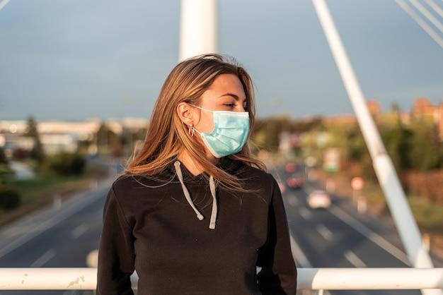 Menina adolescente loira com máscara facial encostado em uma ponte urbana. estrada com carros ao fundo.