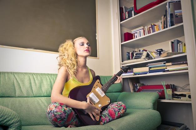 Menina adolescente loira com uma guitarra roxa