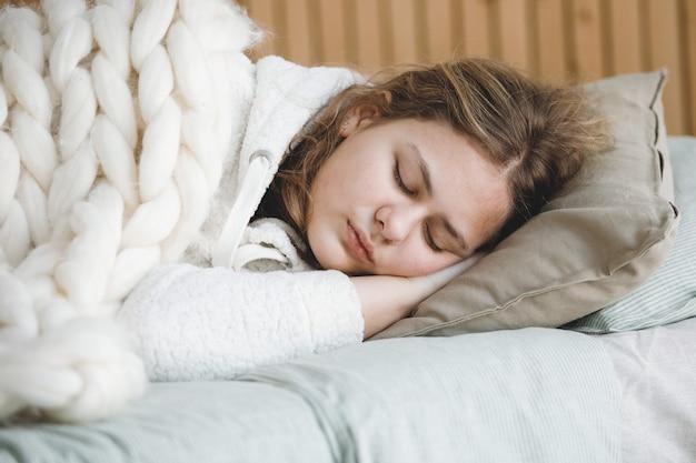 Menina adolescente loira dorme docemente na cama sobre um travesseiro, com as mãos sob a cabeça