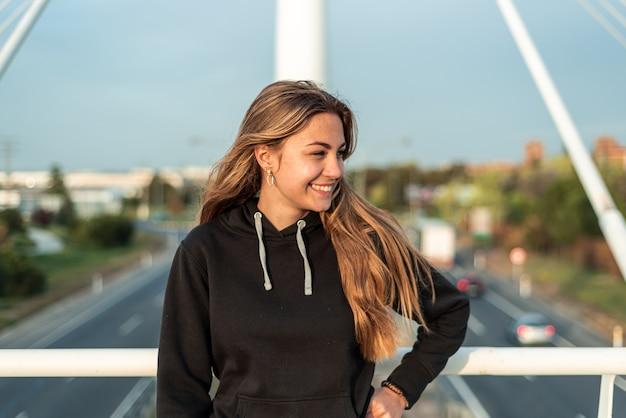 Menina adolescente loira sorrindo em uma ponte urbana. estrada com carros ao fundo.