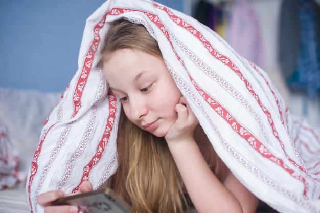 Menina adolescente, mentiras, ligado, um, cama, cobertor