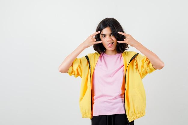 Menina adolescente mostrando gesto de rock n roll, mostrando a língua em uma camiseta, jaqueta e olhando alegre, vista frontal.