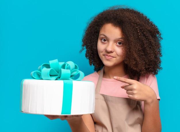 Menina adolescente muito afro com um bolo de aniversário. conceito de padaria