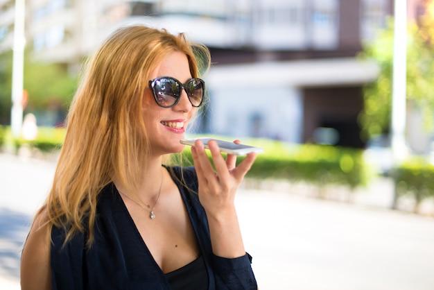 Menina adolescente muito jovem feliz falando ao celular na rua