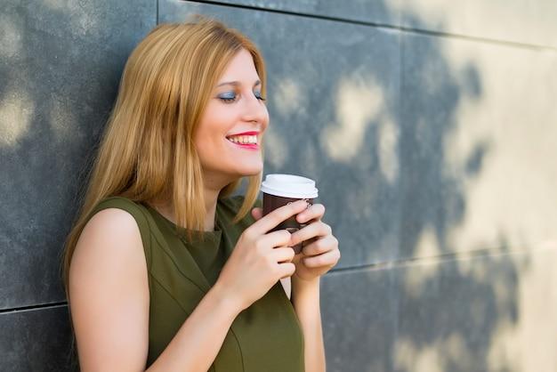Menina adolescente muito jovem feliz segurando café quente no copo de papel para viagem no strret