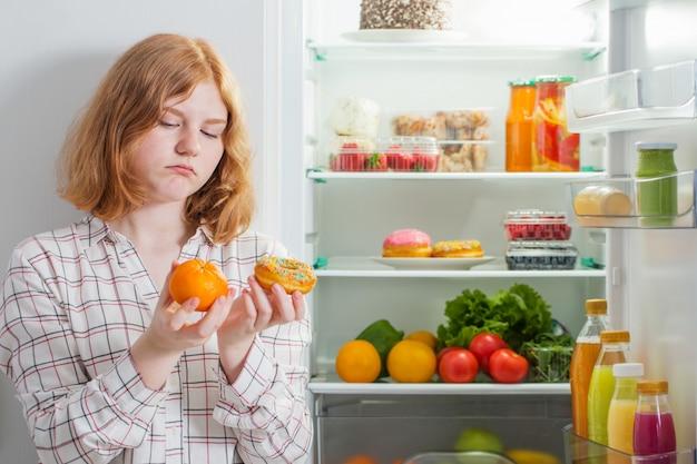 Menina adolescente na geladeira com comida