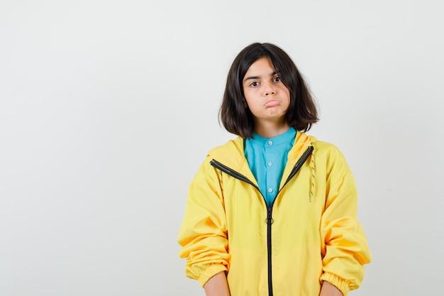Menina adolescente na jaqueta amarela, curvando o lábio inferior e parecendo sem noção, vista frontal.