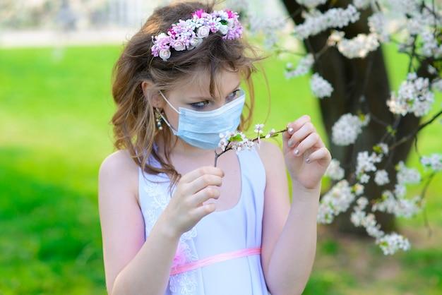 Menina adolescente na máscara médica no jardim florido de primavera. conceito de distância social e prevenção do coronavírus.
