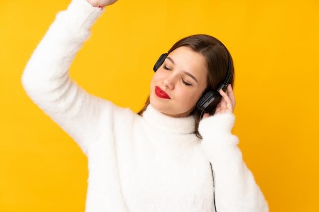 Menina adolescente na música amarela e dança