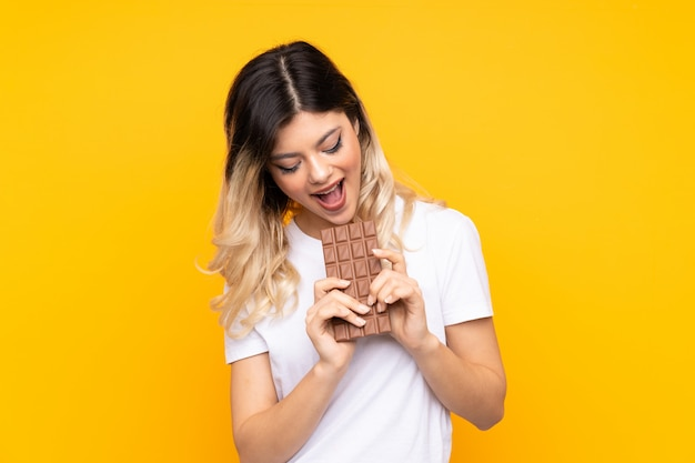 Menina adolescente na parede amarela, comendo uma tablete de chocolate
