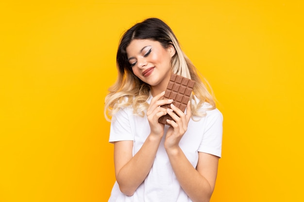 Menina adolescente na parede amarela, tomando um comprimido de chocolate e feliz