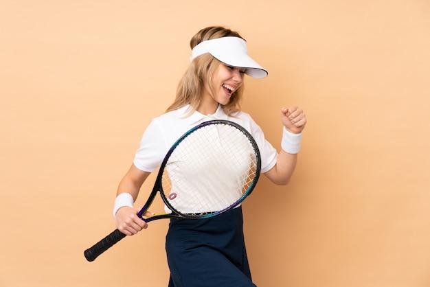Menina adolescente na parede bege jogando tênis e comemorando uma vitória