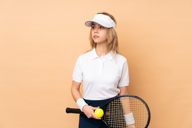 Menina adolescente na parede bege jogando tênis