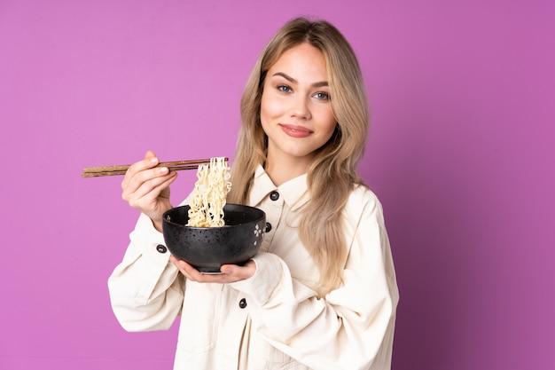 Menina adolescente na parede roxa, segurando uma tigela de macarrão com pauzinhos