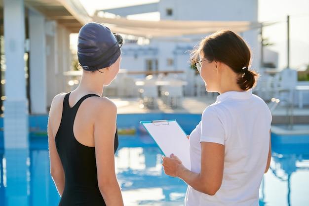 Menina adolescente nadadora com boné de maiô esportivo e treinadora perto da piscina ao ar livre, estilo de vida ativo e saudável dos jovens Foto Premium