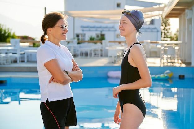Menina adolescente nadadora com boné de maiô esportivo e treinadora perto da piscina ao ar livre, estilo de vida ativo e saudável dos jovens