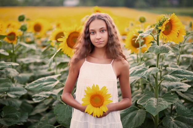 Menina adolescente no campo de girassóis em um dia de verão.