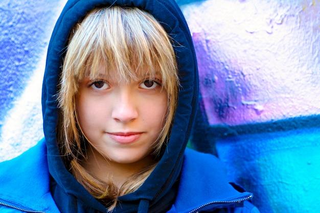 Menina adolescente no capô em uma rua da cidade. estilo de rua da juventude.