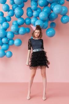 Menina adolescente no cone do aniversário que levanta na parede cor-de-rosa e no contexto azul dos balões.