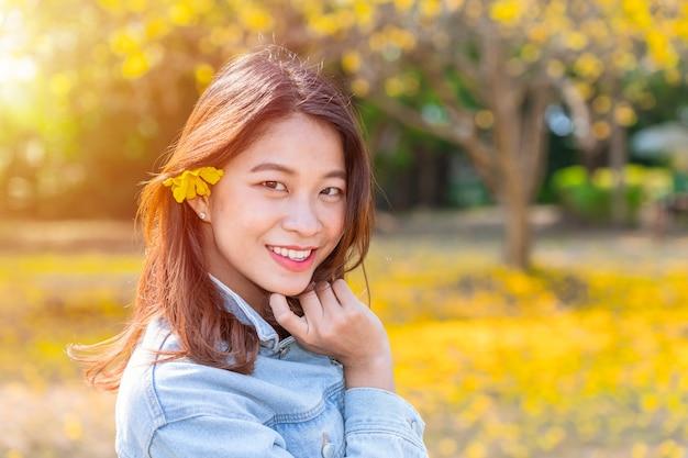 Menina adolescente nova asiática bonita com outono da flor do amarelo da natureza.