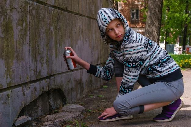 Menina adolescente olhando em volta com tinta spray, prestes a escrever um graffiti na parede
