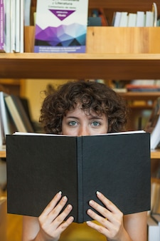 Menina adolescente olhando para a câmera por trás do livro
