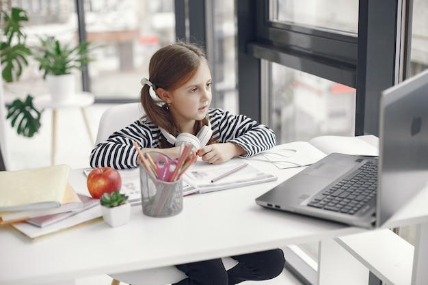 Menina adolescente olhando para o laptop. criança no período de isolamento de quarentena durante a pandemia. educação escolar em casa. distanciamento social. teste escolar online.