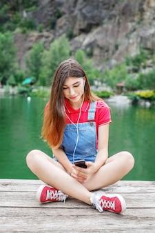 Menina adolescente ouve música em fones de ouvido no cais.