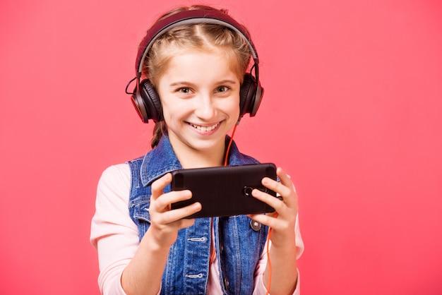 Menina adolescente, ouvindo música em fones de ouvido e segurando smartphon