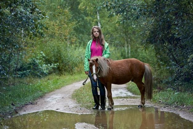 Menina adolescente parada com um cavalinho na estrada com grandes poças no campo no verão