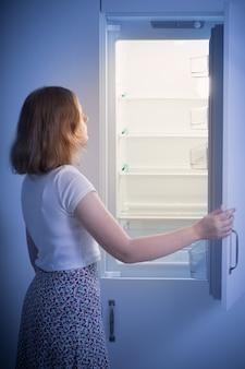 Menina adolescente pela geladeira vazia