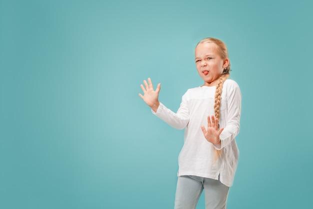 Menina adolescente pensativa duvidosa que rejeita algo contra o azul