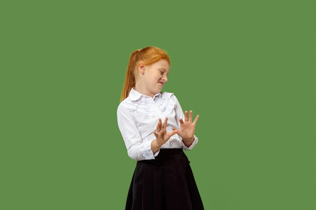 Menina adolescente pensativa duvidosa que rejeita algo contra o verde