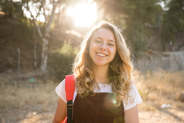Menina adolescente positiva sorrindo na natureza