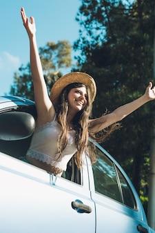 Menina adolescente que acena felizmente através do carro.