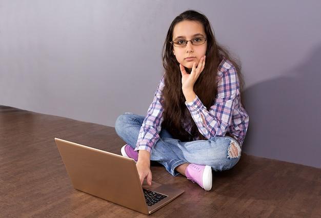Menina adolescente que senta-se no assoalho na frente de um portátil.