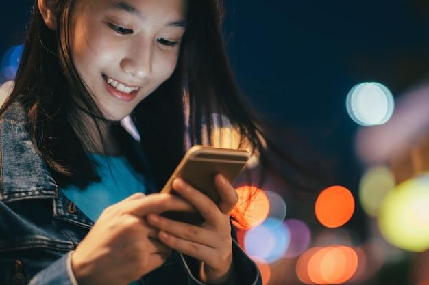 Menina adolescente que usa o telefone móvel para conversar e enviar a mensagem.