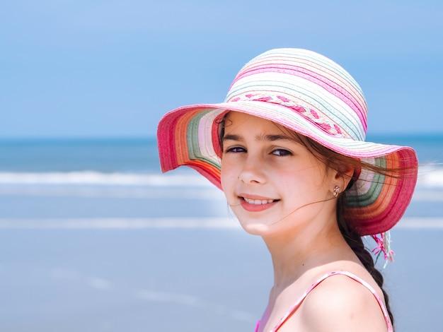 Menina adolescente que veste no chapéu e no roupa de banho coloridos que aprecia a vista na praia tropical.