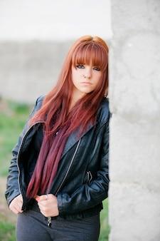 Menina adolescente rebelde com cabelo vermelho, encostado na parede