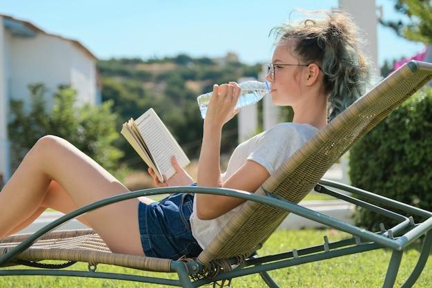 Menina adolescente relaxante livro de leitura ao ar livre e água potável